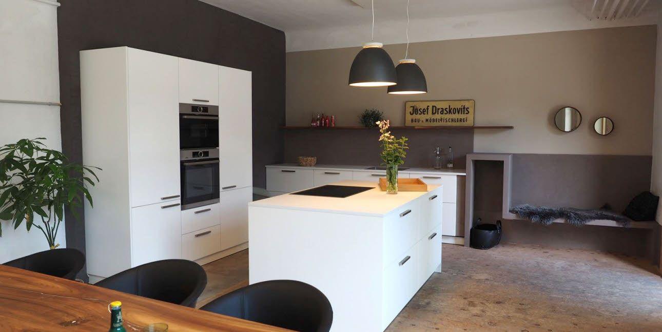 Eine zeitlose, weiße Küche vor einer Wand in trendigem ...