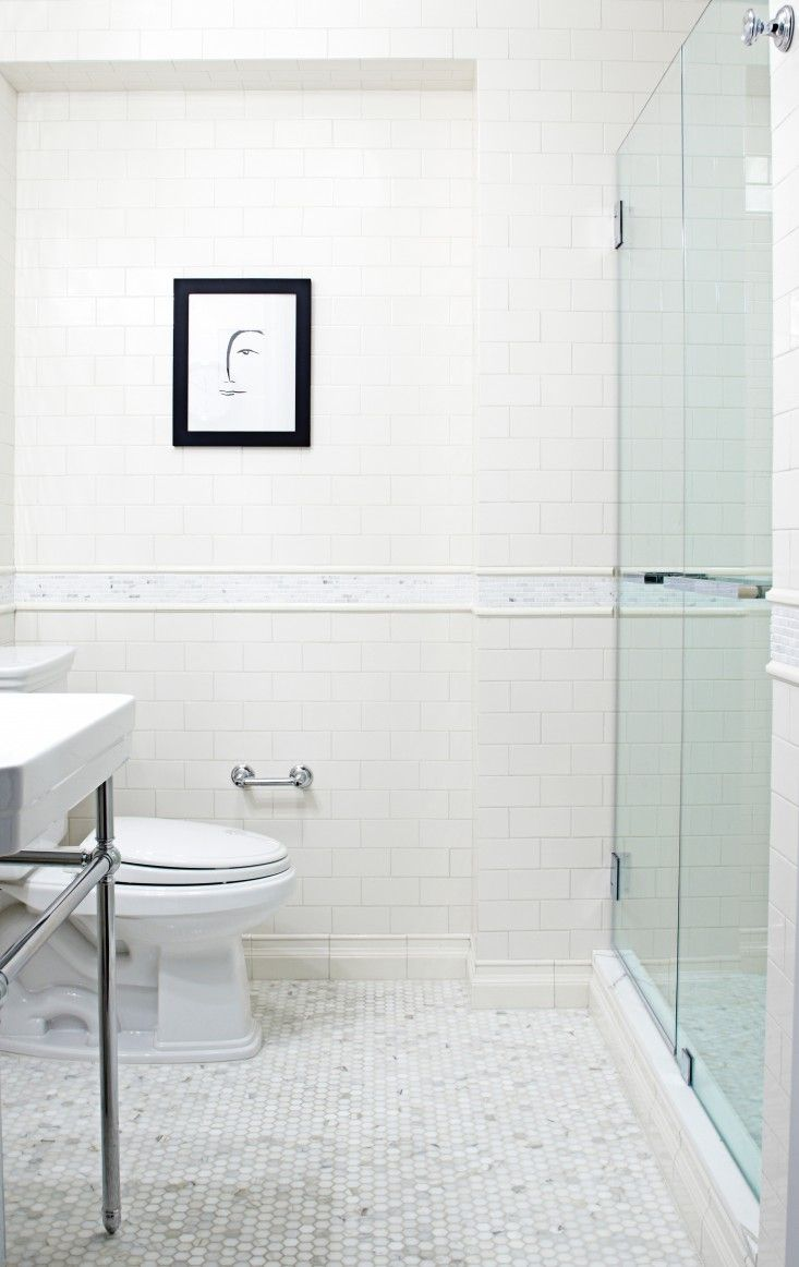 Simple white bathroom dressed up with tile baseboard and mosaic ...