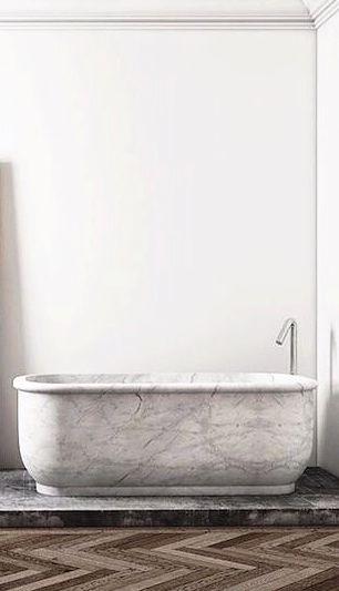 Marble tub with clean faucet & herringbone floors