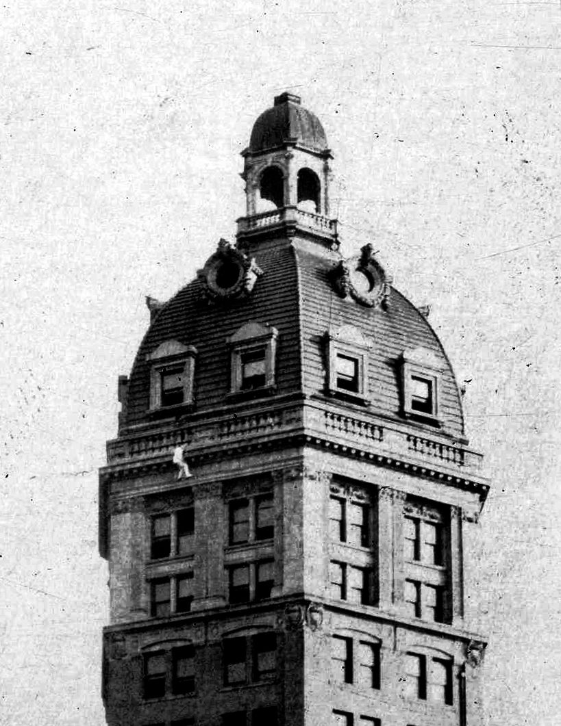 """The Human Fly climbs the Sun Tower in 1918.  Harry Gardiner was a stunt man who earned his living climbing tall buildings in North America and Europe, with no special gear aside from hishighly developed fingers. In Vancouver, the """"Human Fly""""climbed the Hotel Vancouverand then the World Tower on the corner of Beatty and West Pender. He wore white so as to be visible to the """"seething solid mass of humanity"""" that came out to watch. The climb took about an hour and a half."""