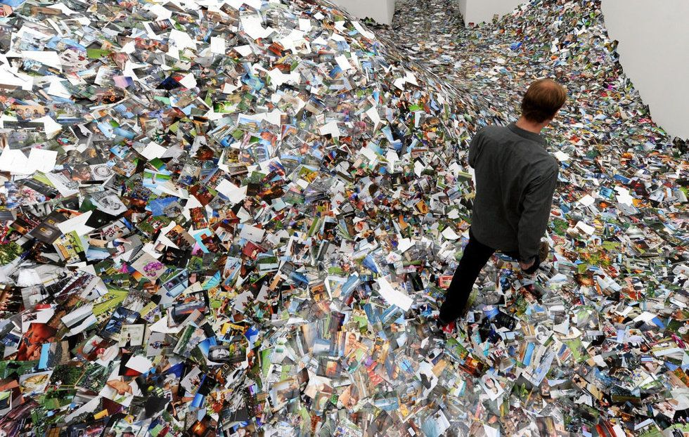 A visitor trudges through an installation of 1 million photos posted ...
