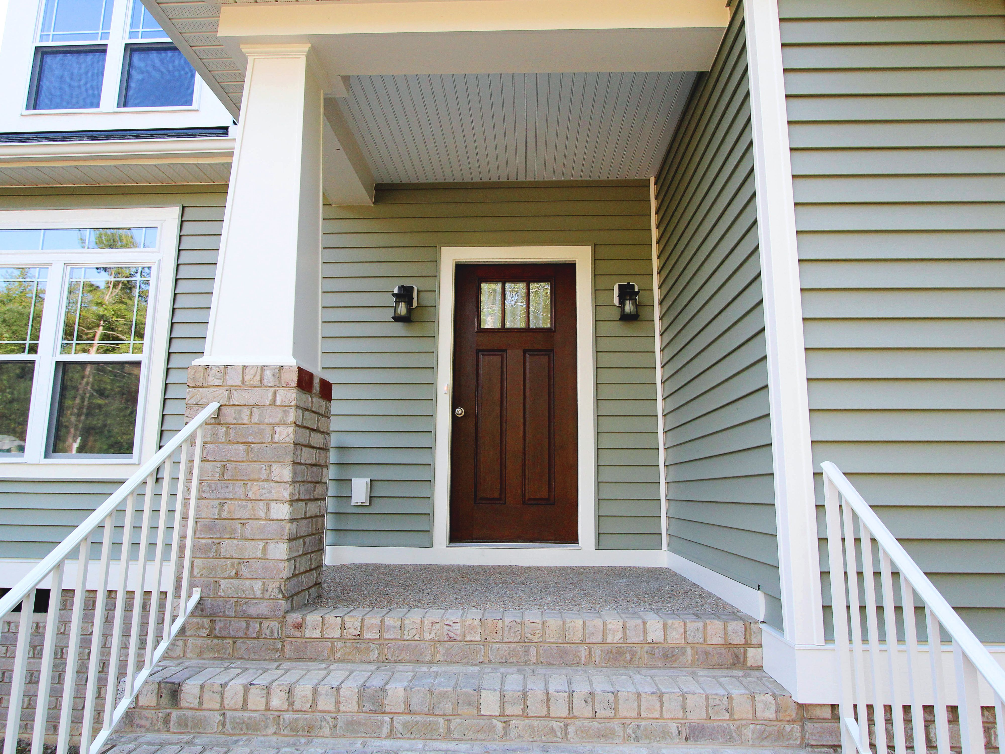 Classic Entryway With White Trim Sage Green Siding And A Wood Front Door Craftsman Style C Bald Green House Siding House Paint Exterior Green House Exterior