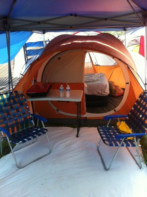 lawn chairs outside tent in corner with blankets on floor