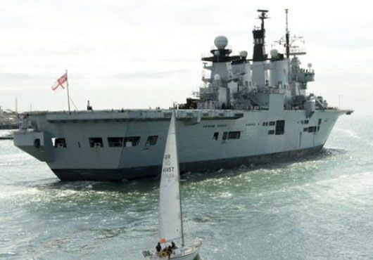 Lusty Casts Off for Cougar 13. Helicopter carrier HMS Illustrious races a yacht.