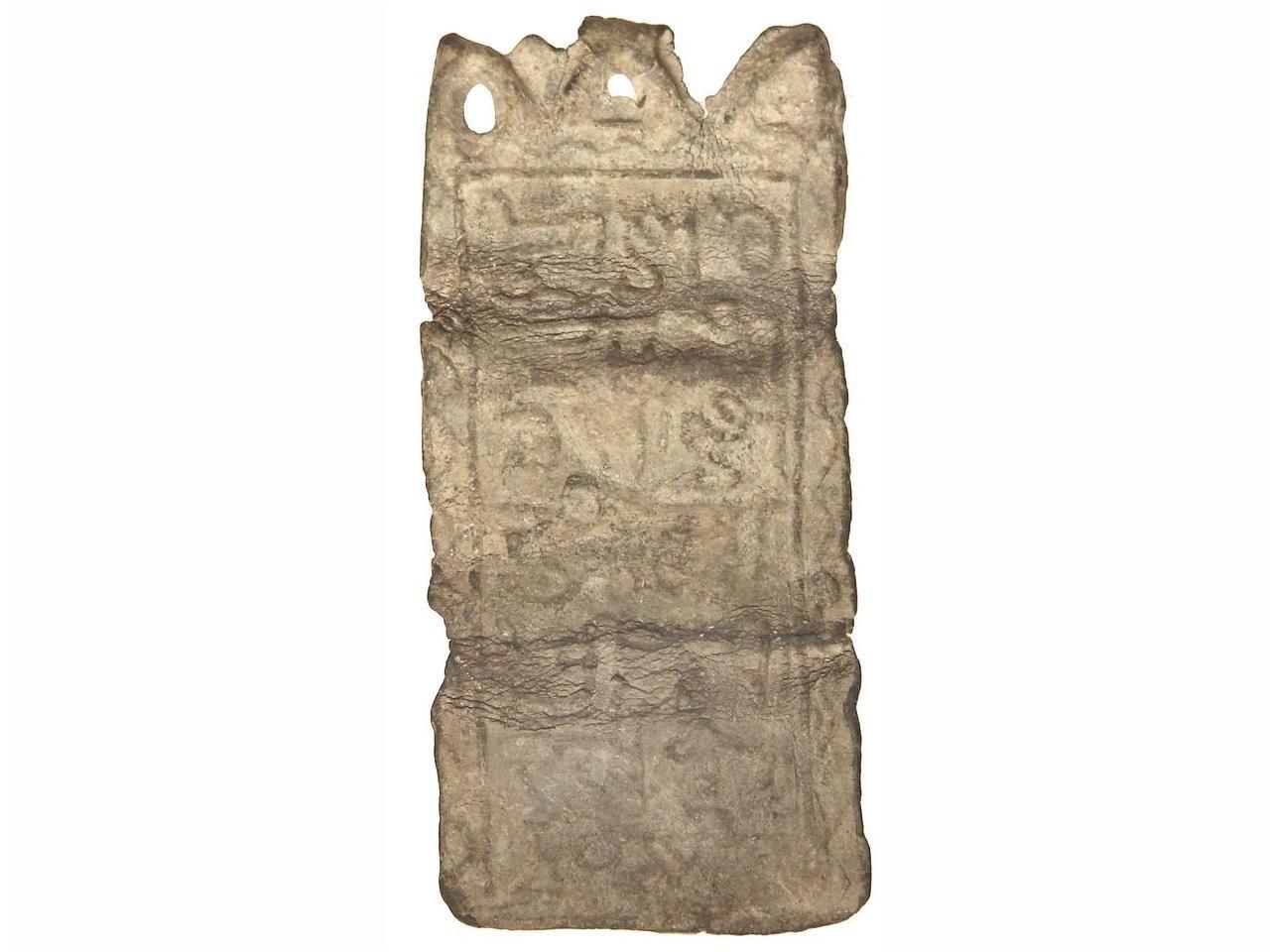 Lote: 3051 MONEDAS HISPANOÁRABES. Plomo. ¿CALIFATO?. 10,17 grs. Amuleto de plomo en forma de plaqueta rectangular (47x22 mm.) con señal de haber estado doblada en tres partes para contener en su interior un pergamino con plegarias. Epigrafía cúfica en ambas caras, que por el estilo, puede fechar la pieza probablemente a la época califal. Conserva los aros de sujeción. MUY INTERESANTE. MBC. SOLERYLLACH.COM