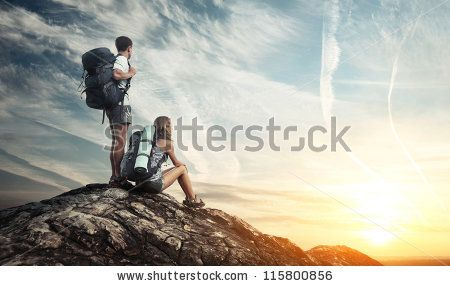 Two tourists with backpacks enjoying sunset on top of a mountain by Dudarev Mikhail, via Shutterstock