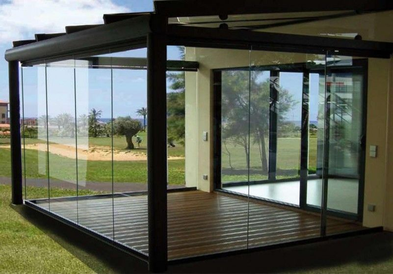 Glass Patio Enclosure Overhang From House Providing Full Roof