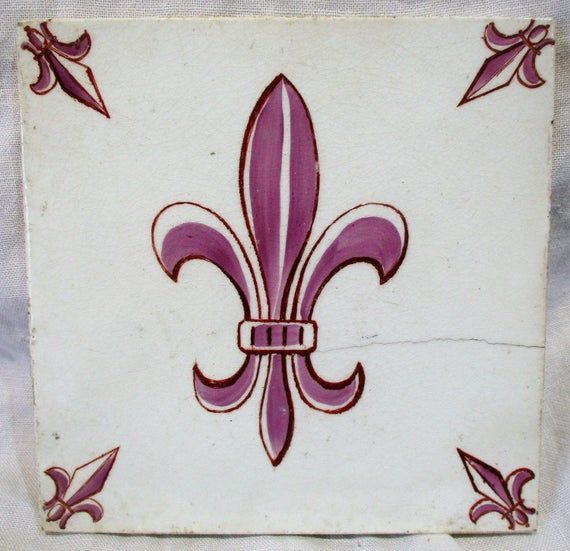 This is a beautiful and old tile with simple stylized hand painted fleur de lis decoration in the center and arrow or spear points in all four corners. Probably from the 1950s, this could be even older, and it appears French but could be Dutch. The back of the tile has two things embossed: