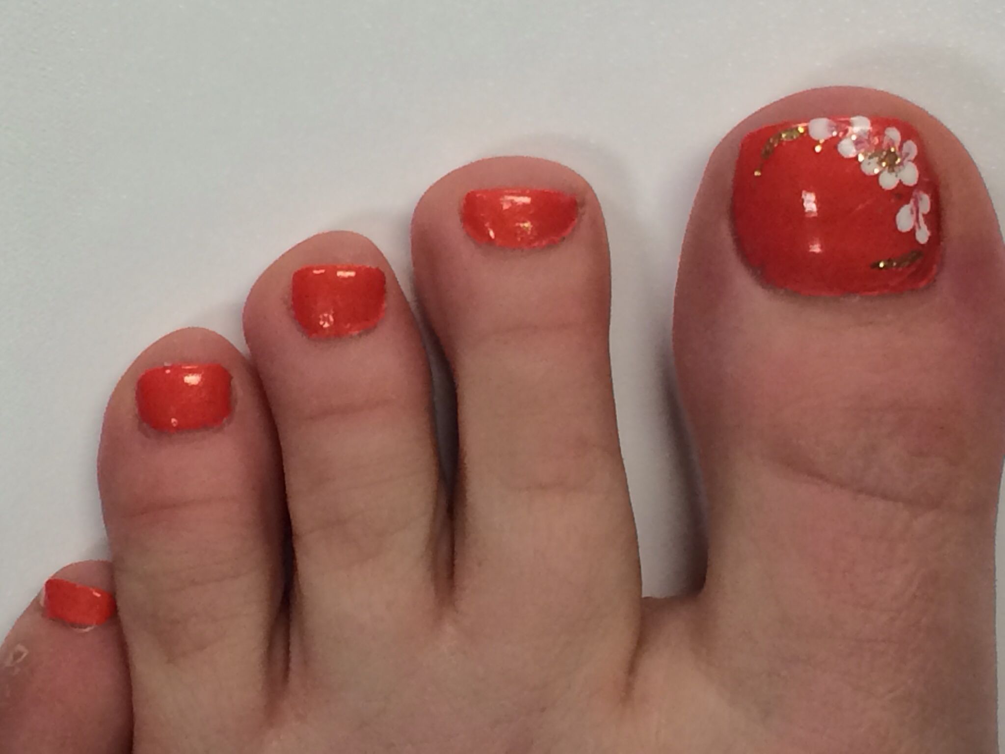coral pedicure with white flower