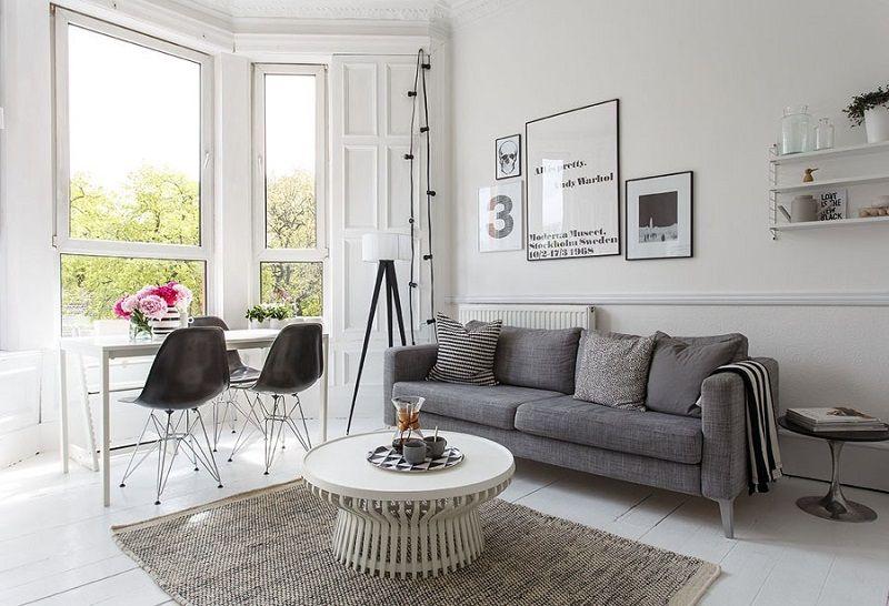 table basse style scandinave ronde, canapé droit gris et chaises design Eames