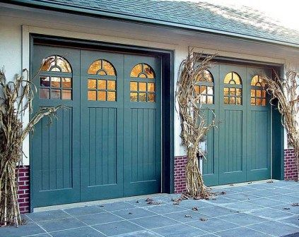 If your goal is to show off your garage door rather than camouflage it, paint  it an accent color-here,
