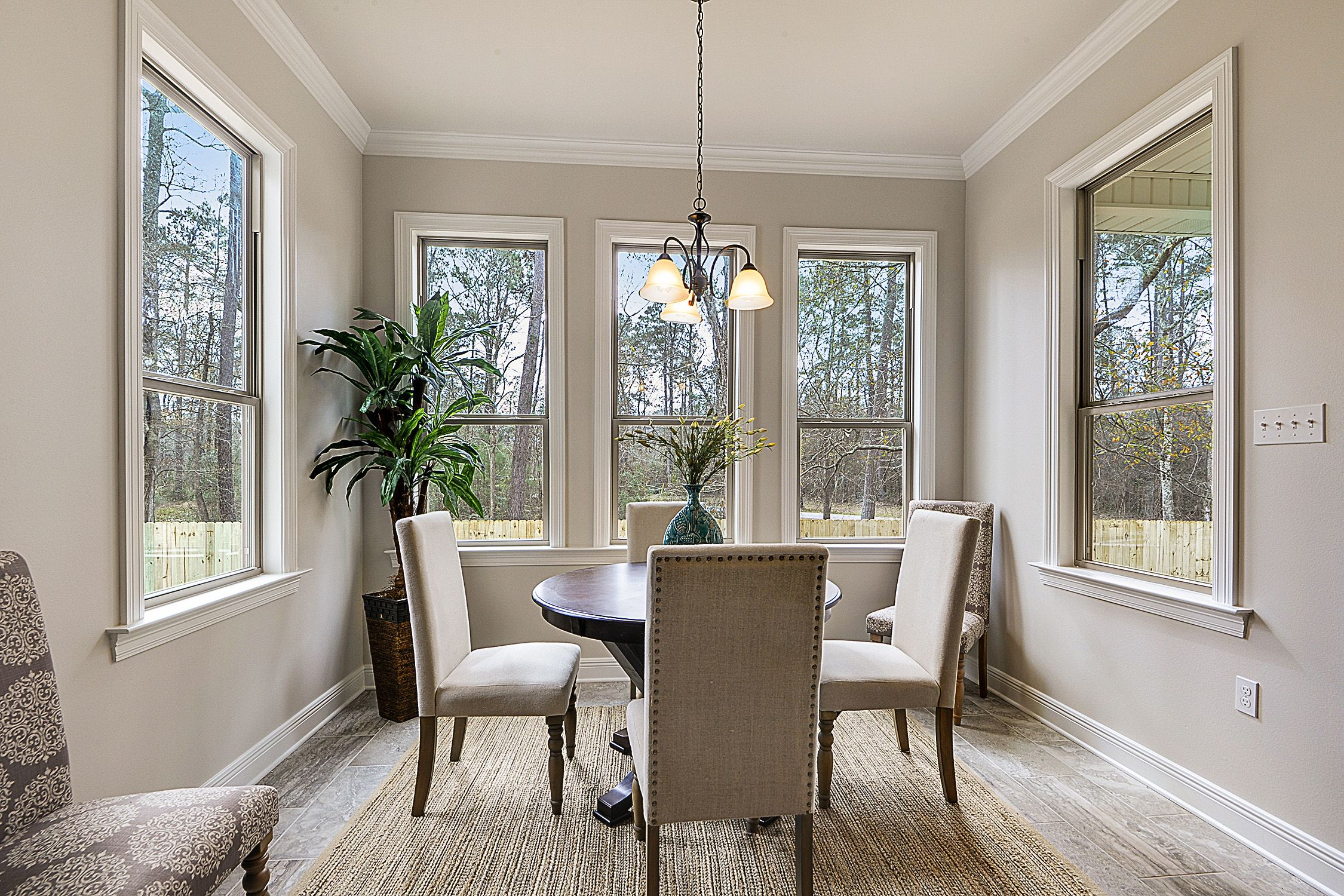 The breakfast nook/eating area is surrounded by windows