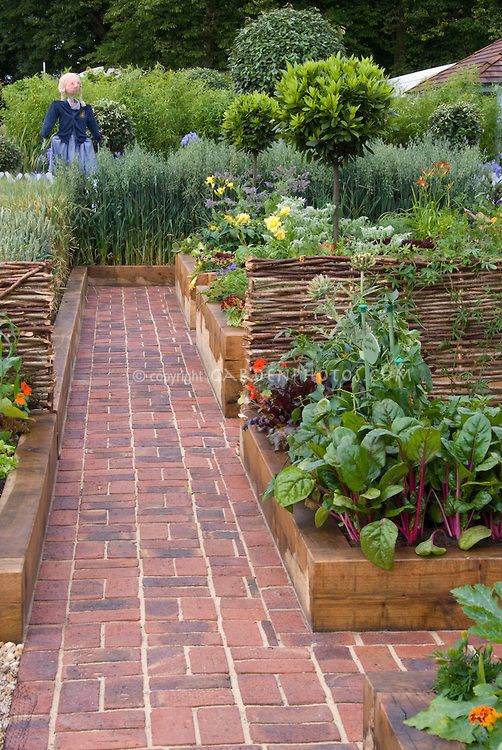 Brick path through beautiful raised bed vegetable gardens for Attractive vegetable garden fence