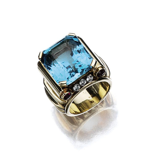 AQUAMARINE, RUBY AND DIAMOND RING, SEAMAN SCHEPPS, CIRCA 1950.   The emerald-cut aquamarine weighing approximately 16.50 carats, within a band of ribbed gold accented with 4 round rubies and 6 round diamonds, size 5 ½, signed Seaman Schepps.