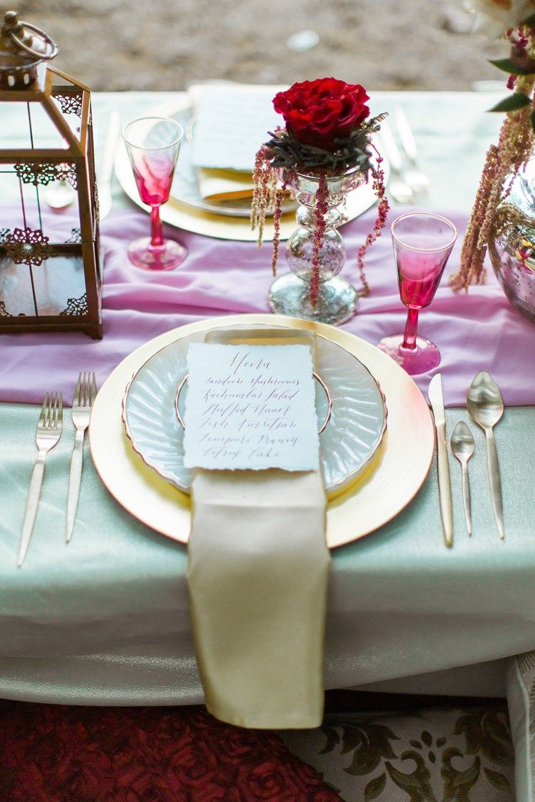 Formal outdoor place setting for modern Indian wedding | A single marsala rose sits in a mercury glass pillar candle stand with pink amaranthus draping over the edges | White and gold plates are used with ombre magenta sherry glasses to bring a pop of color | Snowdrop Photography