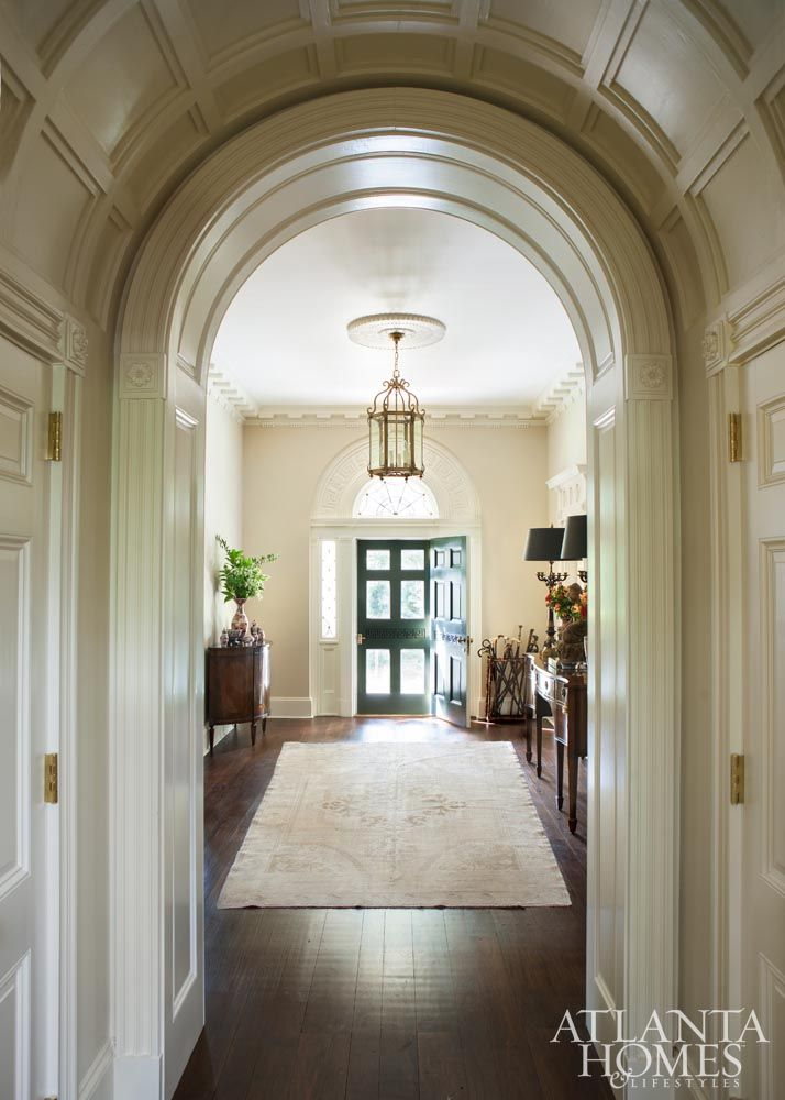 A grand foyer and center hall show off plaster molding, a barrel ...