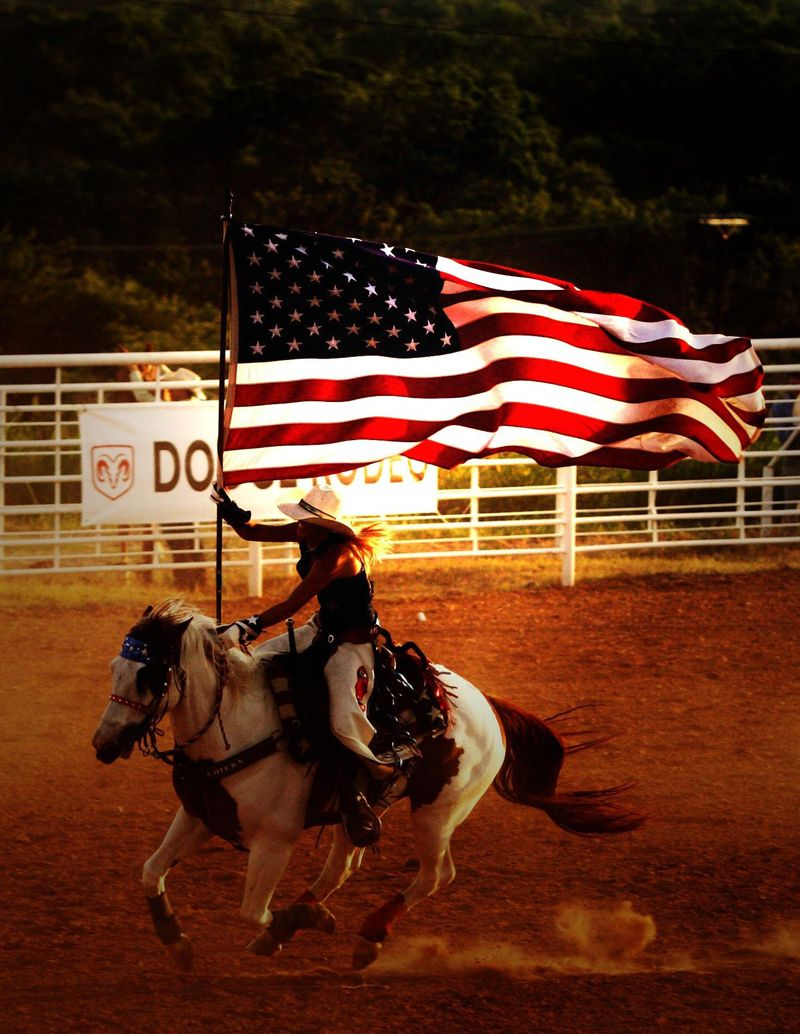 Galloping horse with rider carrying American flag waving in
