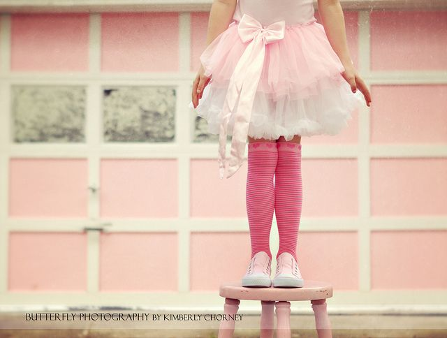 Standing on a Pink stool, wearing pink shoes, pink socks, a pink tutu, in front of a pink house... This is a true story!