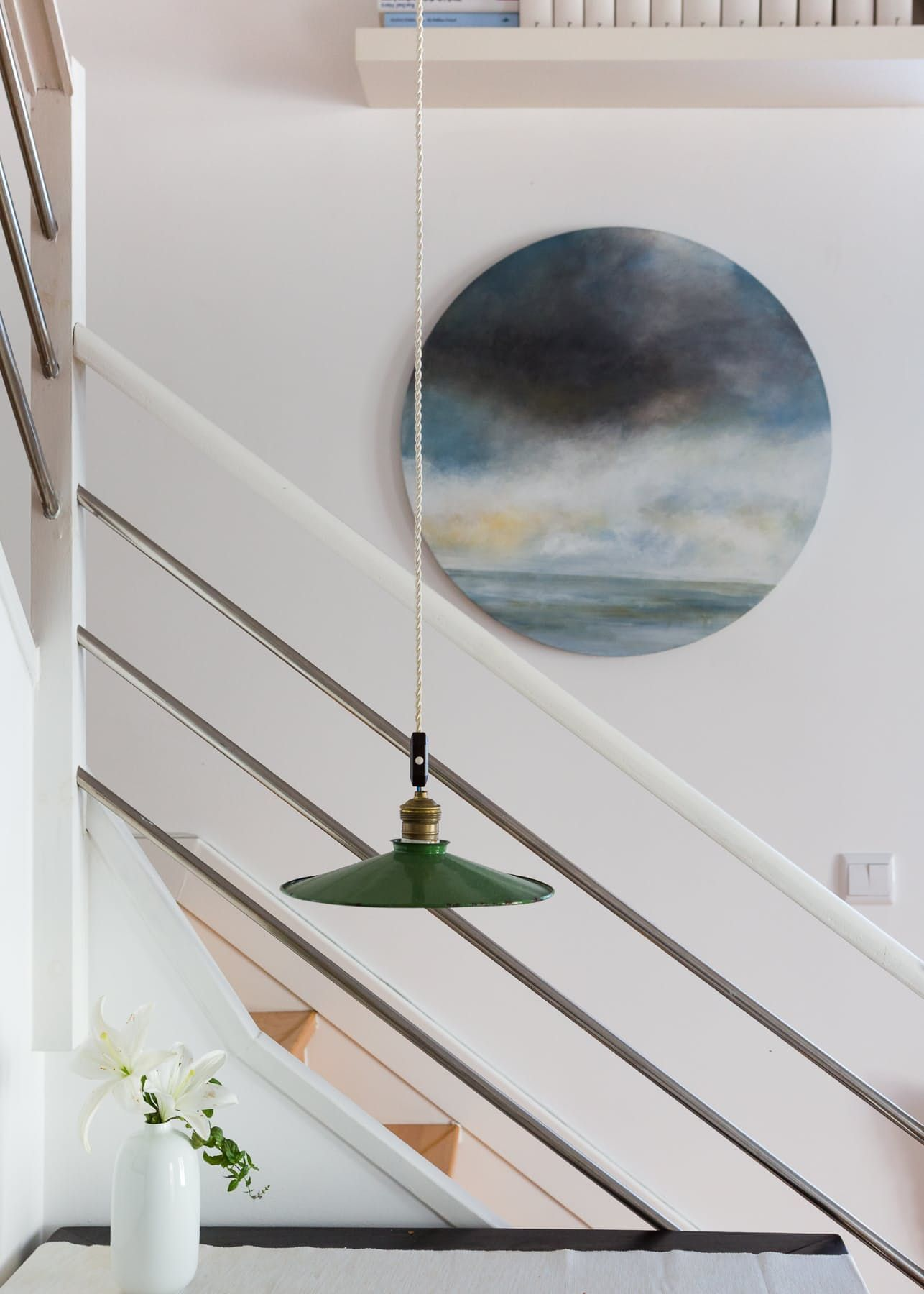 """The cloud painting is by Antje, and hangs in the space where she   likes to let pieces """"rest"""" for a while before moving to their new homes. The green lamp is reassembled from different old lamp parts."""