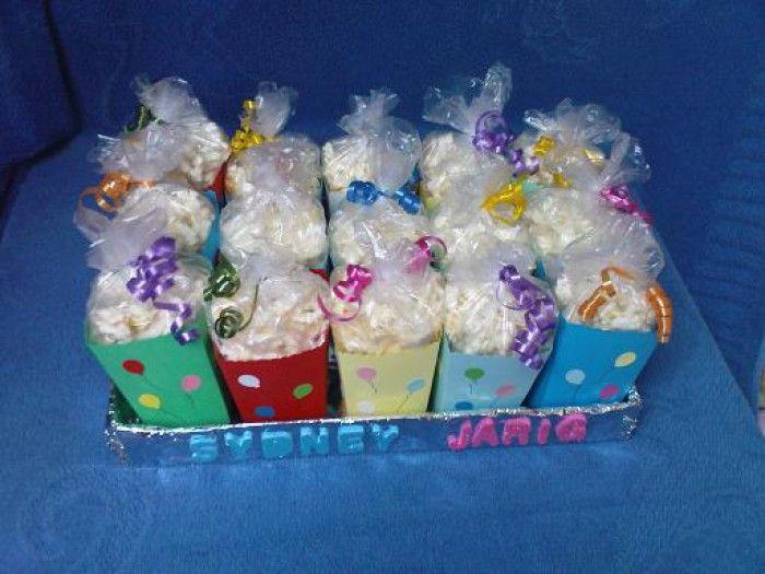Leuke simpele traktatie: popcorn in vrolijke bakjes, inpakken in doorzichtig folie met gekleurde strikjes eromheen.