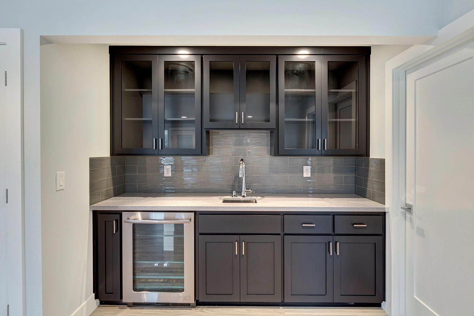 Basement Bar Kitchen With A Wine Bar White Quartz Counters And Glass Cabinets Uppers Greatnwhomes Billjohns Basement Bar Bars For Home Basement Kitchenette