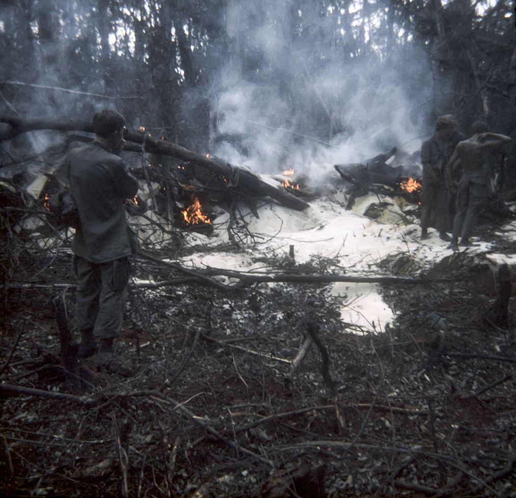 Effort to burn captured rice at NVA supply base inside Cambodia. - Vietnam War