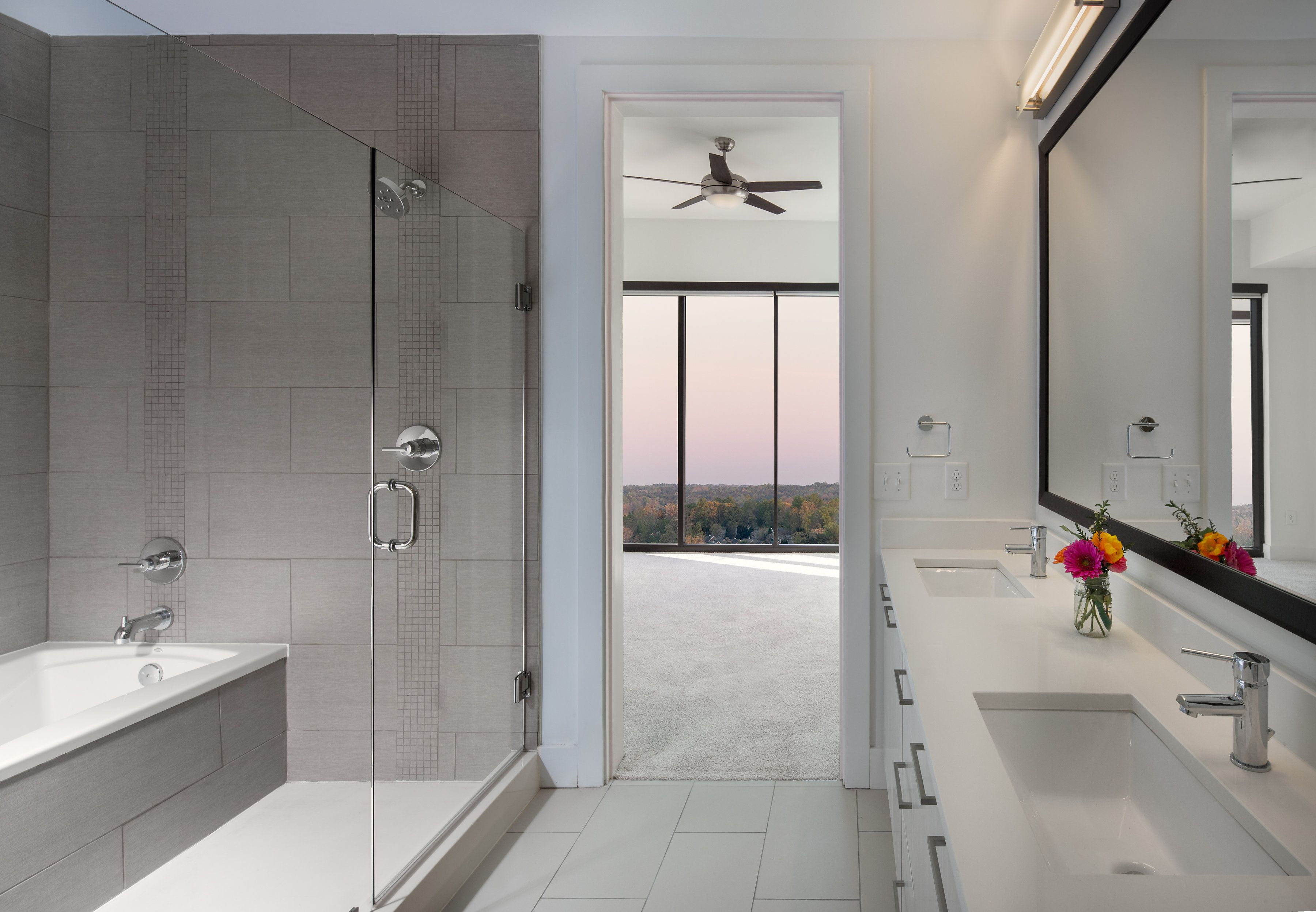 A frameless glass shower, tub, and double sinks round out this flawless, contemporary modern bathroom.