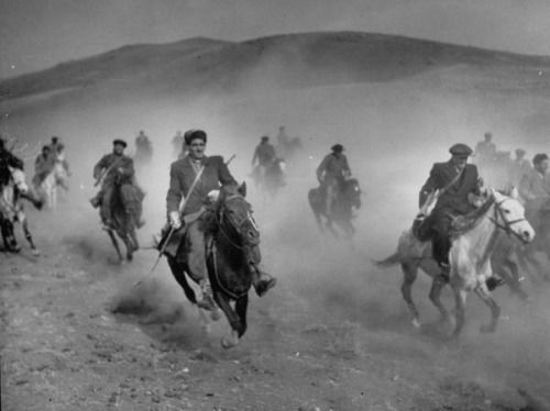 Rifle-toting horsemen of Shahsavan tribe galloping into a sandstorm in the hills of eastern Azerbaijan. Iran, April 1951. Photograph by Dmitri Kessel.