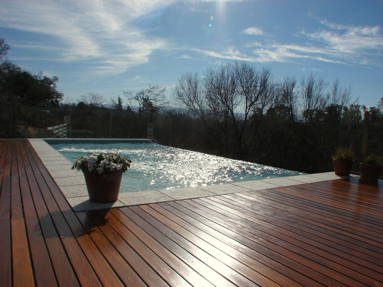 Piscina desborde infinito deck de madera for Diseno piscina