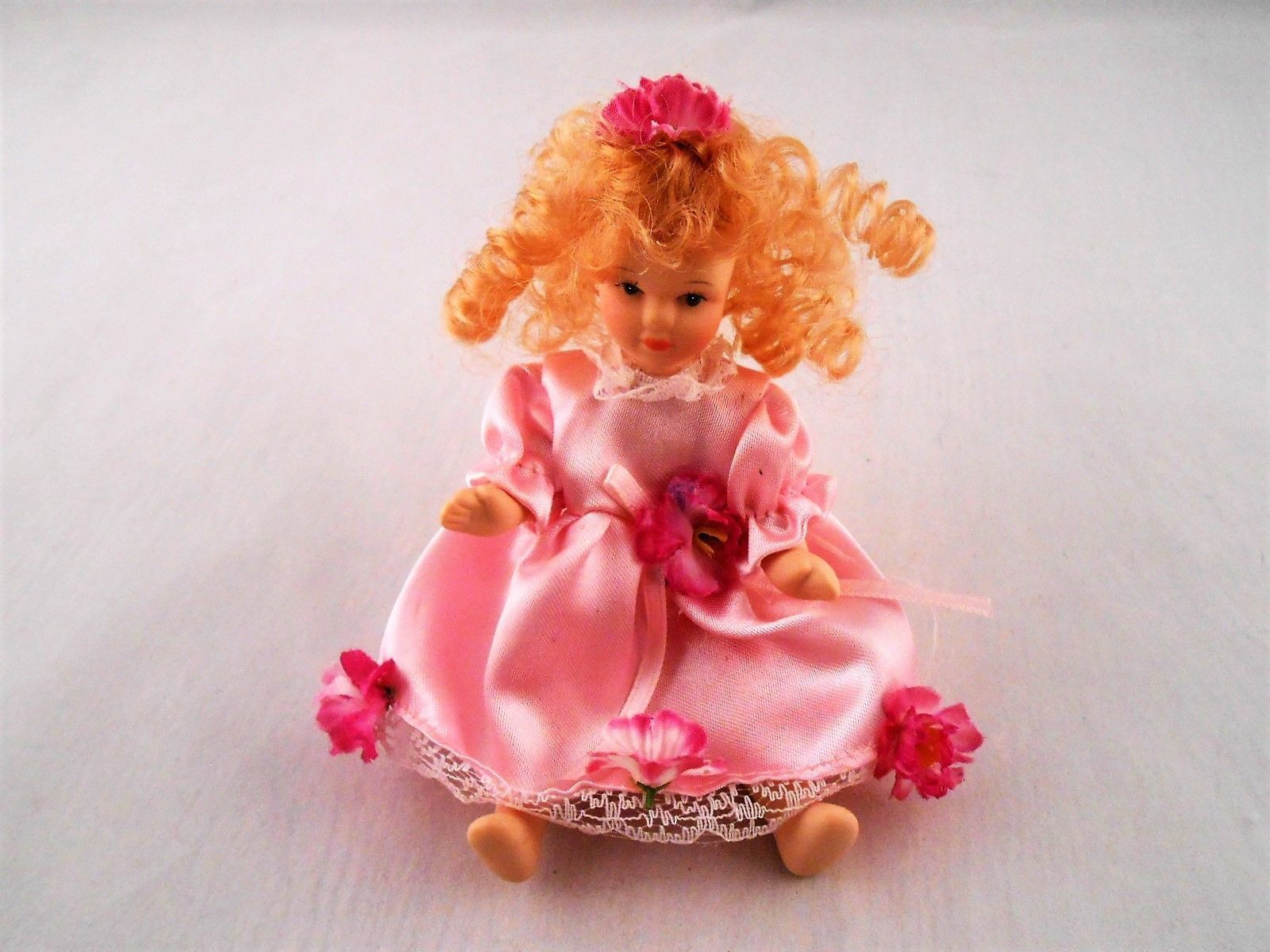 This small vintage porcelain doll can both sit and stand she is