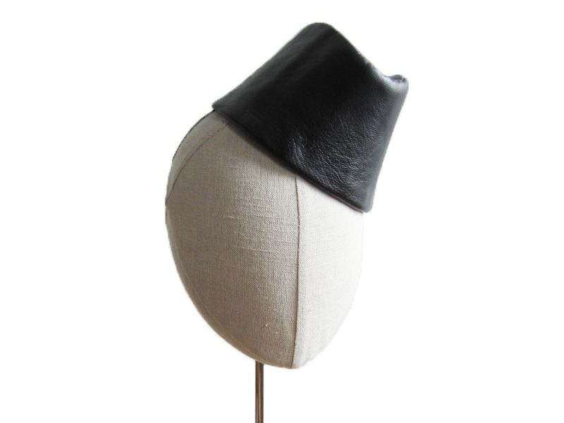 Inspired by the sassy airline stewardesses of the 1940's, this one-of-a-kind hat features hand-blocked black fur felt covered in soft black lambskin leather, French lining and a stretch elastic neck strap. A favorite of actresses, musicians and models, it has been worn by Rose Byrne for InStyle, Shirley Manson for The Block, Constance Jablonski for Vogue Italia, Diana Dondoe for Vanity Fair Italia and Gwen Loos for Elle.