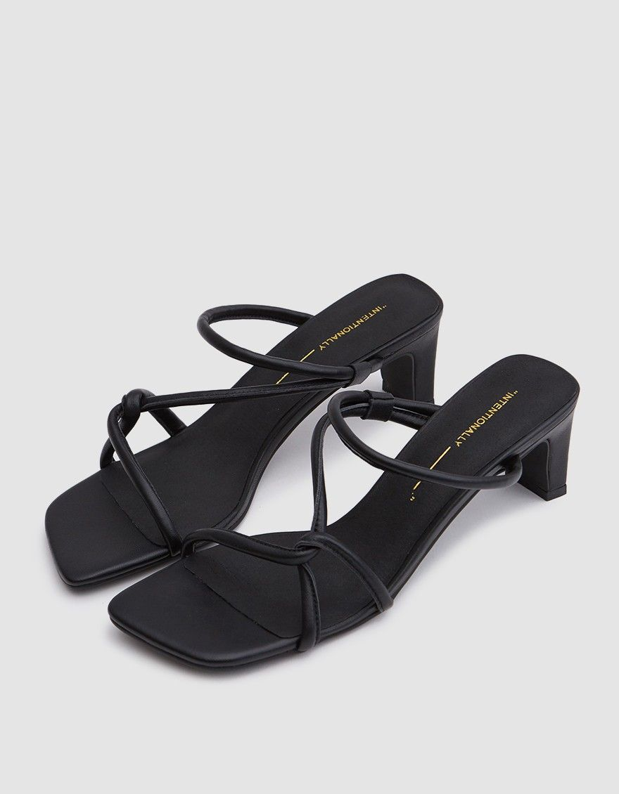 1268ad4294c Strappy heel from Intentionally Blank in Black. Tubular straps at vamp. Square  toe. Padded footbed with gold-stamped logo. Matching squared-off heel.