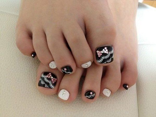 A lace themed toenail art design. Decorate your toenails with alternate matte black and white bases and add frilly white lace paint on top. Enhance the effect with pink and silver beads added on the topmost layer of the design.