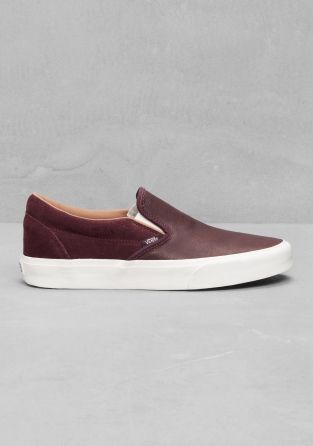 VANS Classic slip-ons featuring a smooth leather upper, fine stitching, and the Vans logo sewn to the outer edge.