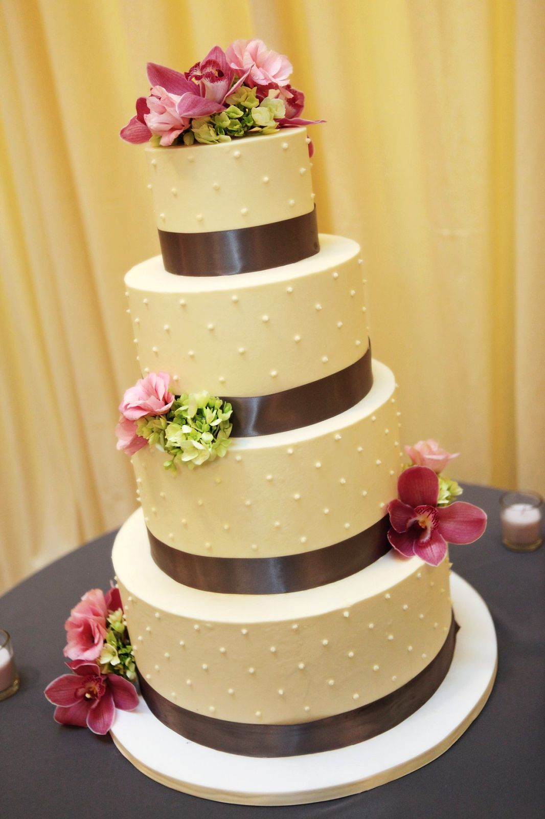 Dot grid patterned wedding cake with pink and green flowers (orchids ...