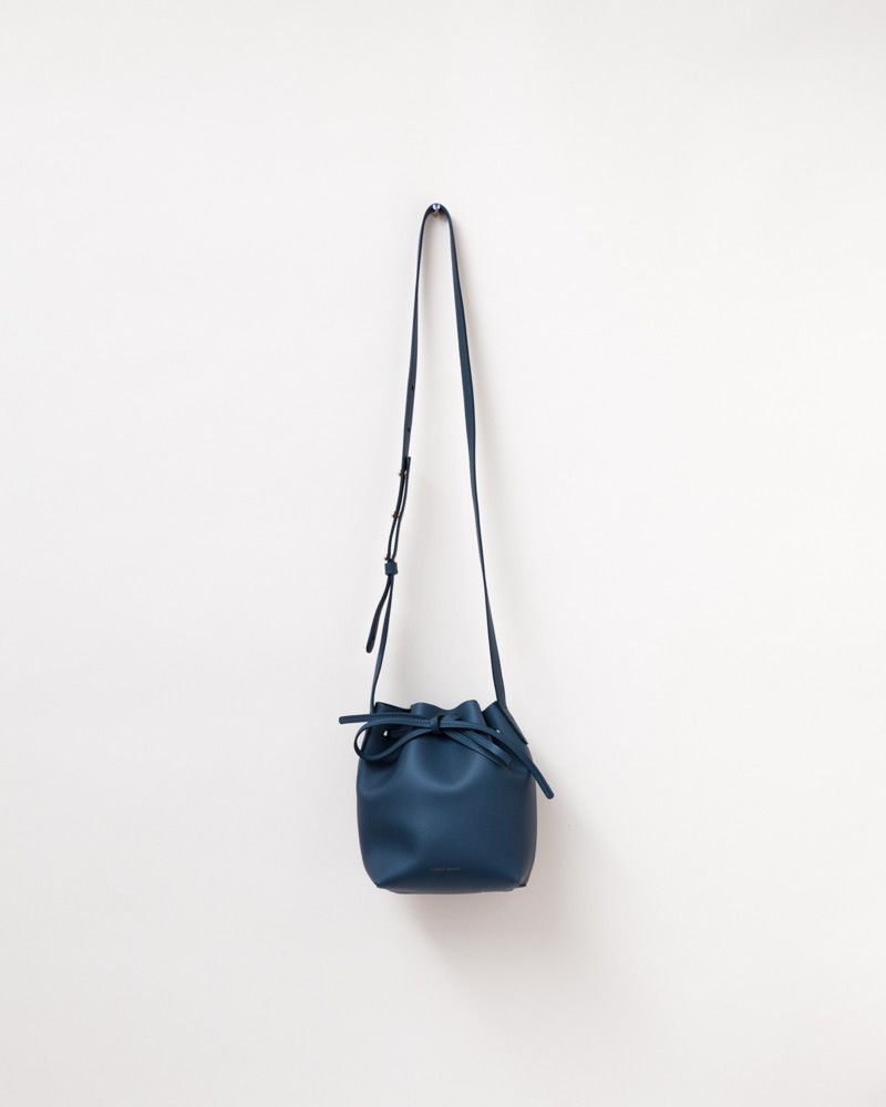 Mini Mini Calf Bucket Bag in Blue/Blue by Mansur Gavriel. Small bucket bag features top cinch closure with leather strands fastened in a bow, adjustable shoulder strap with gold-tone hardware, and mat