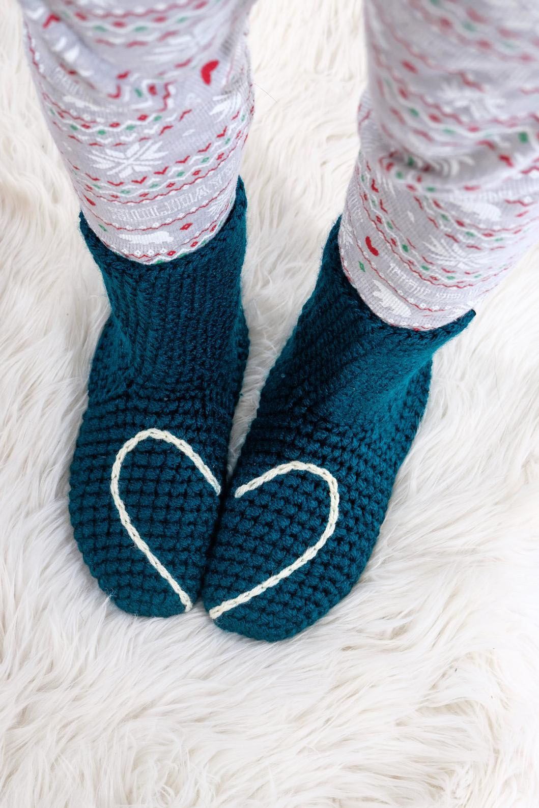 No pair of holiday pajamas are complete without a cozy pair of socks. Chunky handmade slipper socks with a love heart design that shows when your feet stand together. Crocheted with a nice thick yarn, these socks are perfect to use as house or bed socks and there's even a protective layer on the sole to help prevent wear.