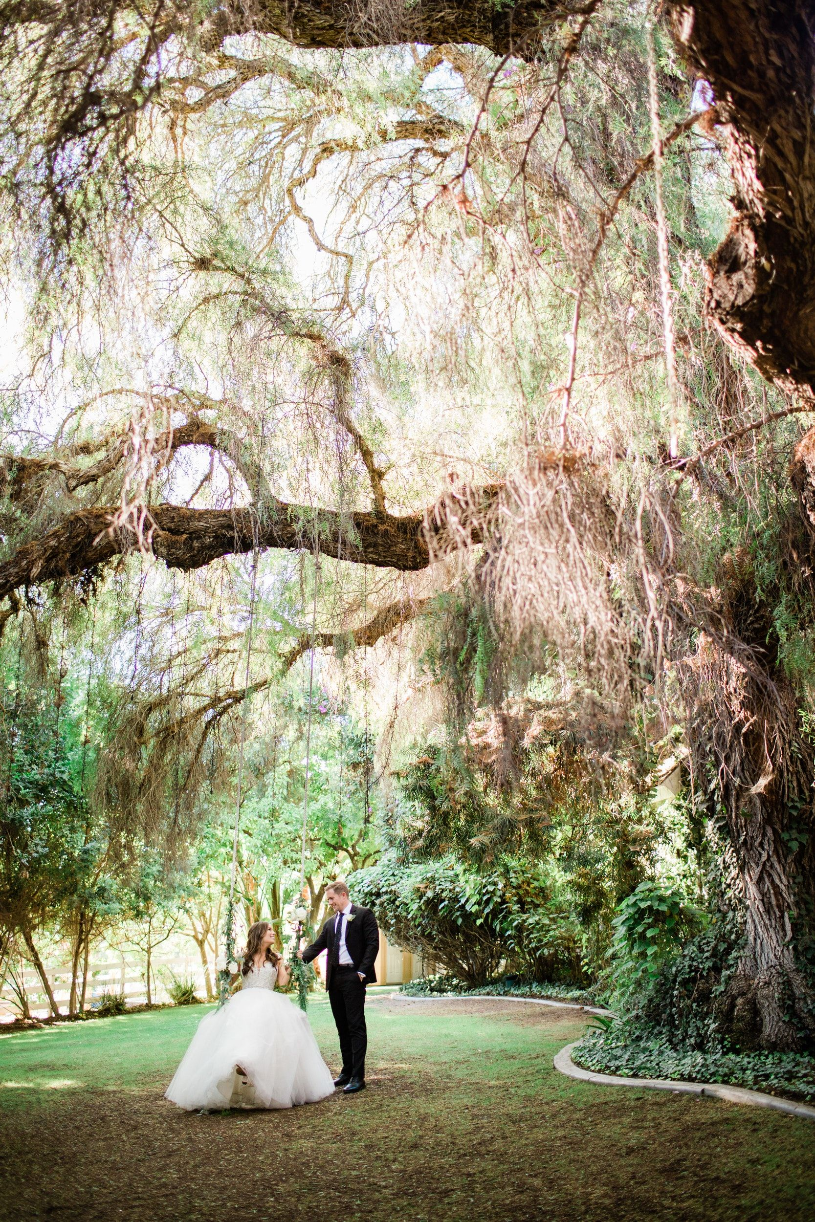 A Massive 200 Year Old Pepper Tree Dwarfs This Newlywed Couple On The Wooden Swing In 2020 Green Gables Wedding Estate Green Gables Garden Venue