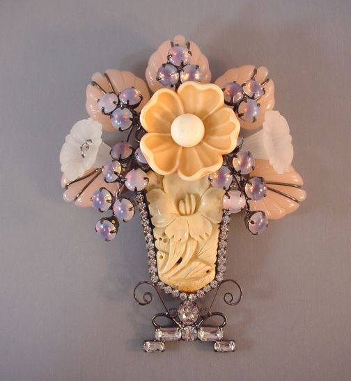 VRBA vase brooch with carved bone vase portion with a floral design, pink, peach and cloud plastic flowers, pink cabochons and clear rhinestones all set in gun metal colored metal, 5-1/8.