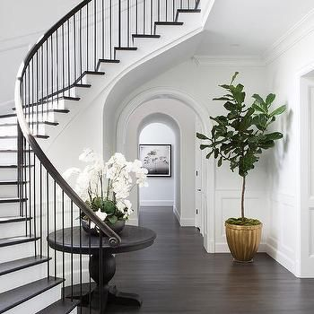 Curved Staircase Wall With Black Round Table Foyer Design Staircase Design Staircase Decor