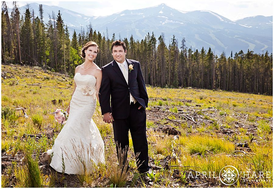 Bride and groom pose for photos in front of the trees and ski resort mountain of Breckenridge, Colorado in July. Location is just off of Boreas Pass Road. - April O'Hare Photography http://www.apriloharephotography.com #Breckenridge #Colorado #ColoradoWedding #BreckenridgeWedding #BreckWedding #FormalWeddingPortrait #SunnyWedding