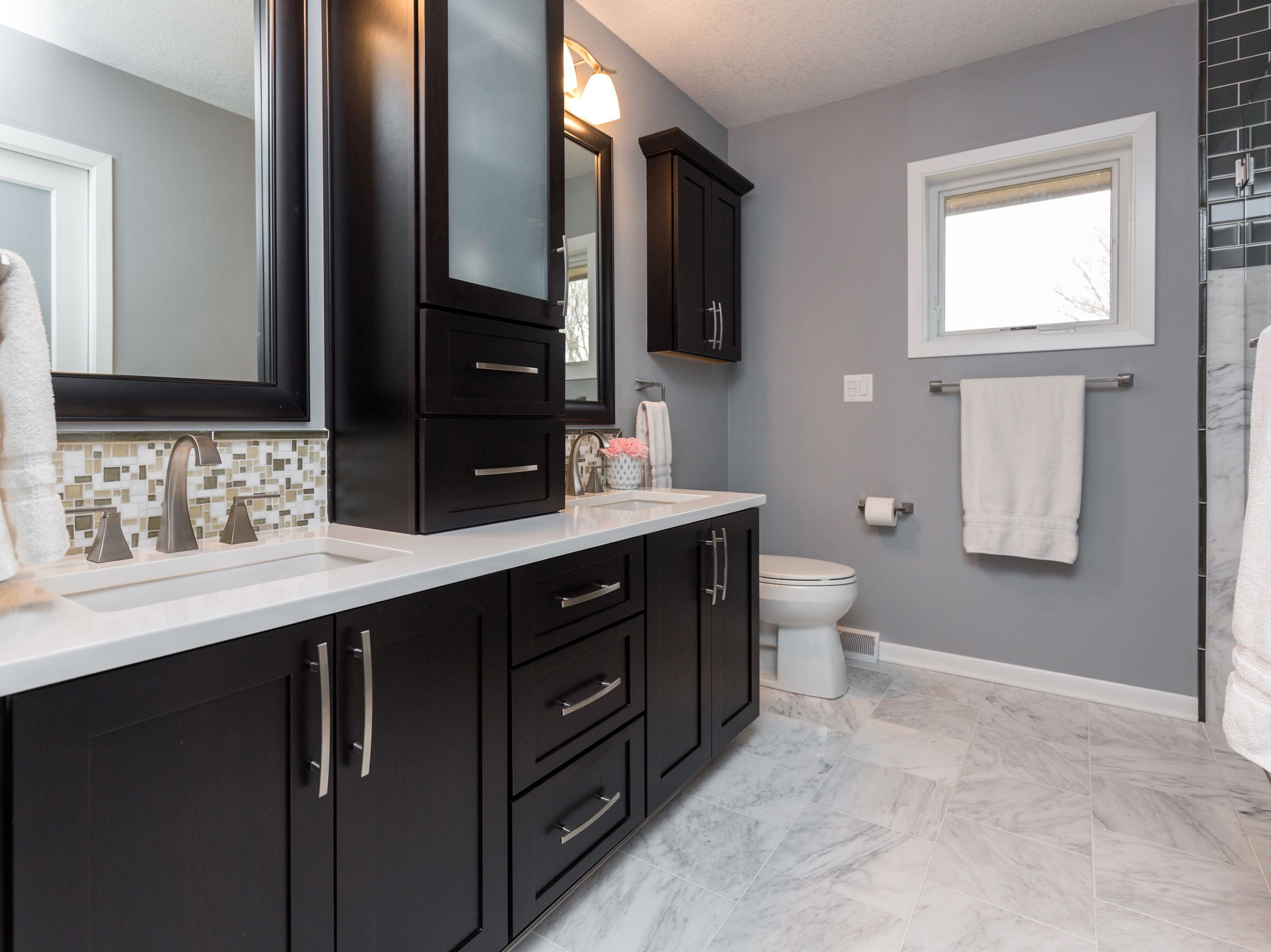 black cabinets in bathroom cabinets white counter tops and a marble floor add 17391