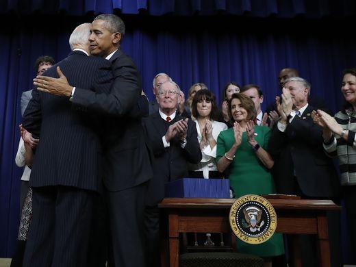 Obama embraces Biden after signing the 21st Century