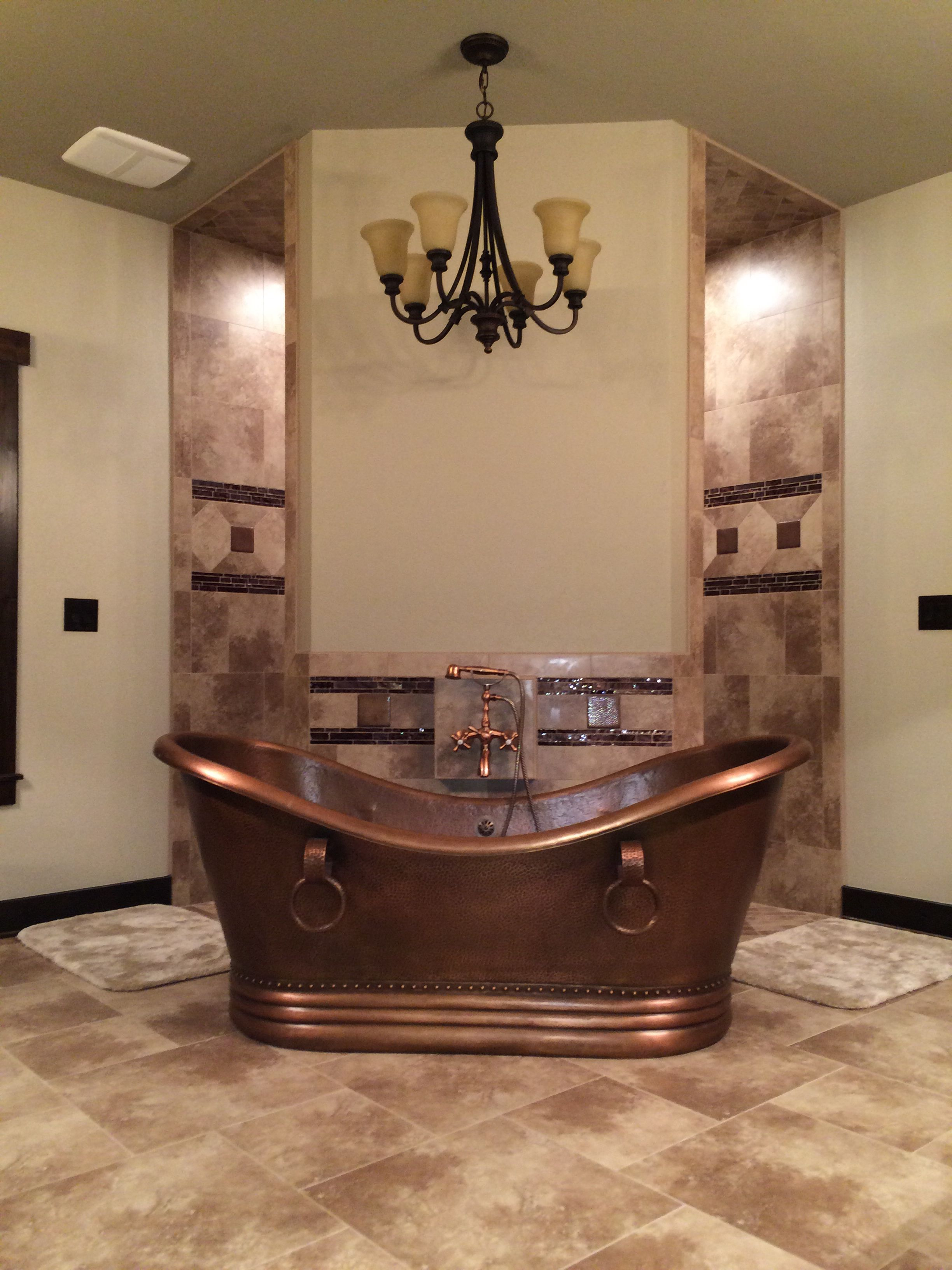 Rustic bathroom, hammered copper tub in front of a corner walk ...