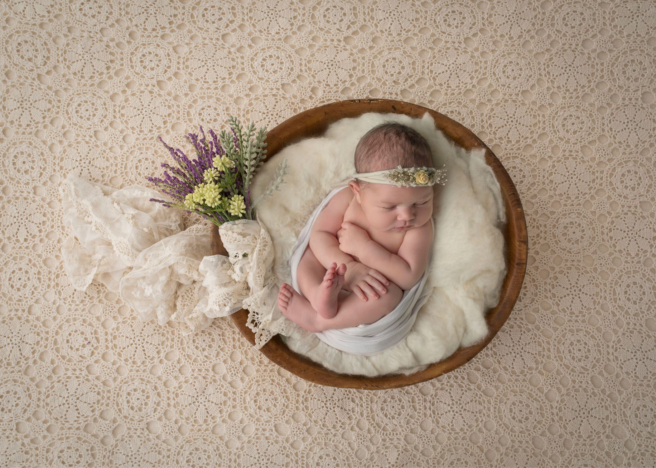 Newborn baby girl asleep in wooden bowl with flowers nearby