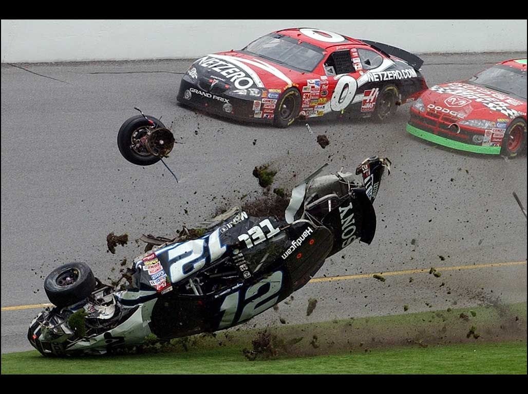Tony Stewart stuck up on top of the tire barrier after contact from ...