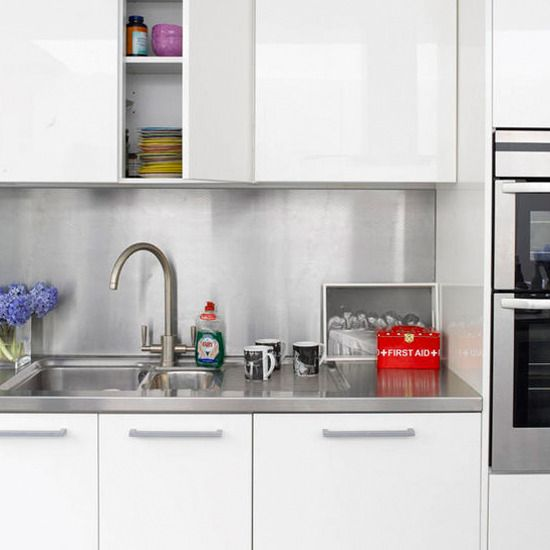 White Kitchen With Stainless Steel Backsplash