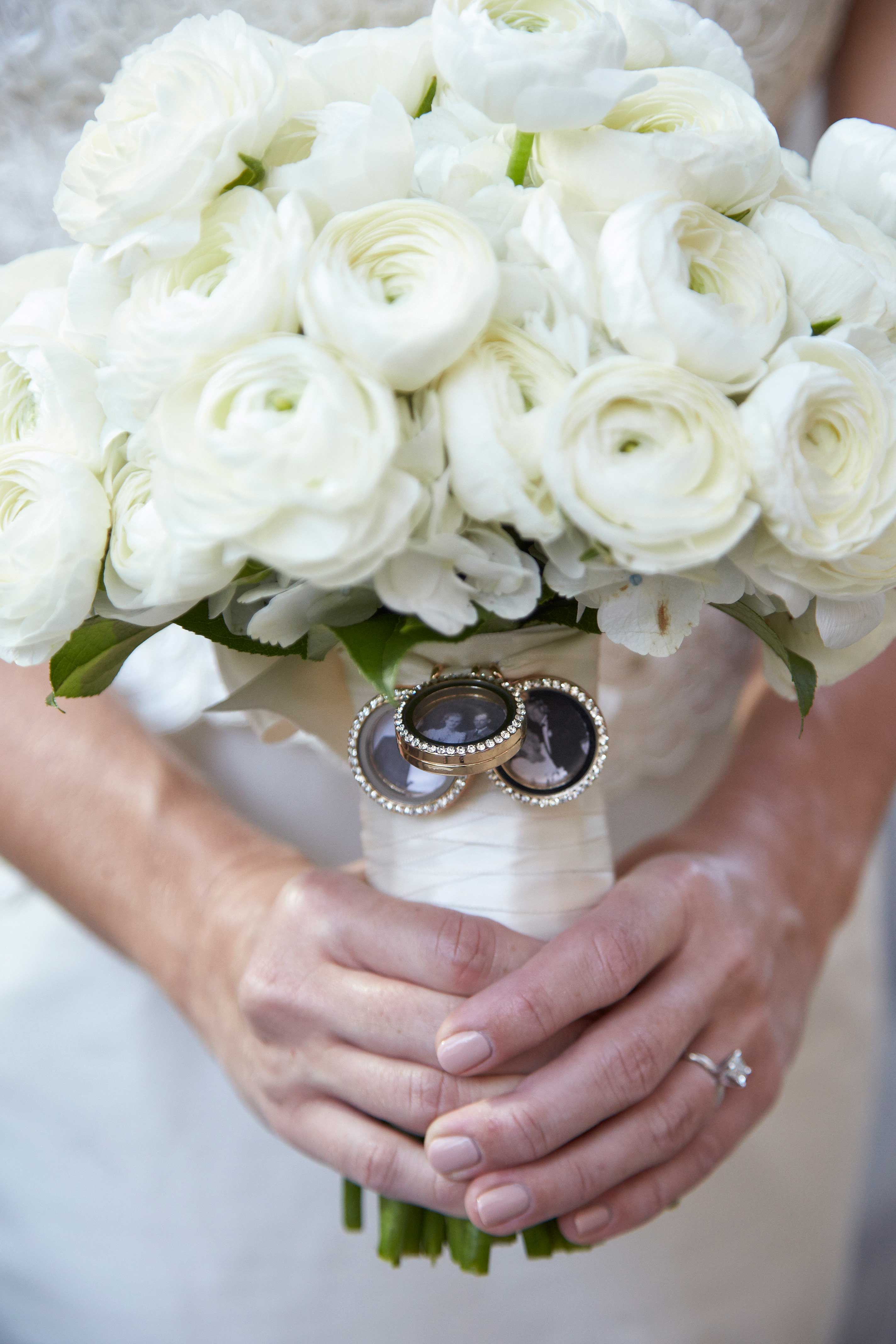 Bouquet of white roses with charms holding family photos of parents grandparents bridal bouquet