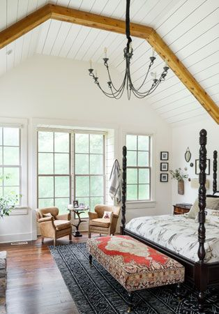 "Vaulted ceilings and shiplap walls create powerful visual impact upon entering the master bedroom itself. Plush linens dress the four-poster bed, while family pieces and collectibles easily blend with comfortable, chic décor. Window seats flank the stone fireplace giving the room a cozy feel and leather club chairs reside in front of imposing windows that reveal an expansive deck, also reimagined by Lee. ""This renovation really is all about the details,"" Lee shares. #vaultedceilingdecor"
