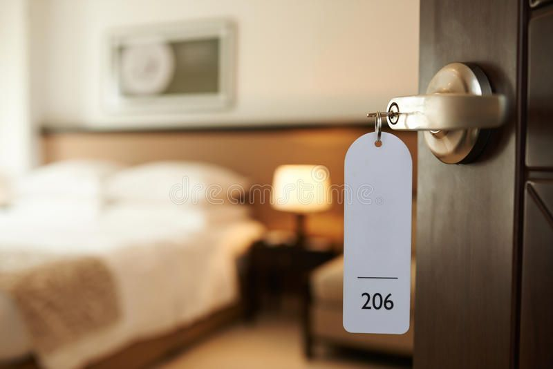 Entering hotel room Opened door of hotel room with key in the lock